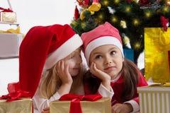 Filles dans des chapeaux de Santa partageant des secrets sous l'arbre de Noël Images stock
