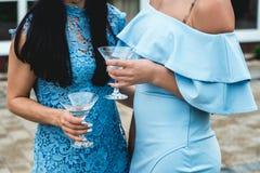 Filles dans des robes bleues avec des verres d'alcool dans leurs mains à la partie Photos libres de droits