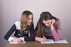 Filles dans l'écriture d'école dans le cahier Images libres de droits