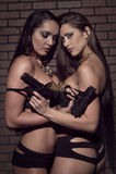 Filles dans la lingerie avec des armes à feu Image libre de droits