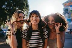 Filles dans la ville feignant pour avoir des moustaches Images stock