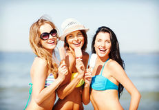 Filles dans le bikini avec la crème glacée sur la plage photos libres de droits