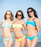 Filles dans le bikini marchant sur la plage Photographie stock