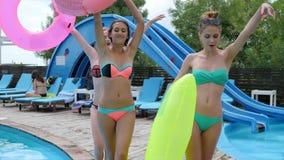 Filles dans le bikini marchant sur le pilier en bois près du poolside avec les anneaux en caoutchouc roses, amies dans le maillot clips vidéos