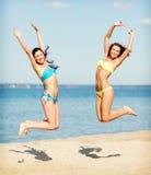 Filles dans le bikini sautant sur la plage Photos libres de droits