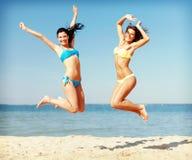 Filles dans le bikini sautant sur la plage Photos stock