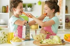Filles dans le cuisinier de cuisine Image stock