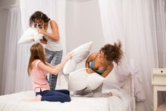 Filles dans le lit ayant le combat d'oreiller dans des pyjamas Photos libres de droits