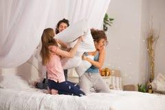 Filles dans le lit ayant le combat d'oreiller dans des pyjamas Image stock