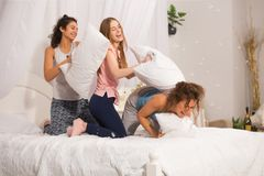 Filles dans le lit ayant le combat d'oreiller dans des pyjamas Photographie stock libre de droits