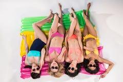 Filles dans les maillots de bain et des lunettes de soleil prenant un bain de soleil sur des matelas de natation Photo libre de droits