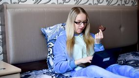 Filles dans leur lit pendant le matin mangeant le dessert, regardant l'ordinateur portable clips vidéos