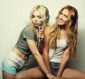 Filles de beauté avec un microphone chantant et dansant Photo libre de droits