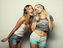 Filles de beauté avec un microphone chantant et dansant Images libres de droits