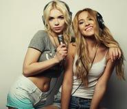 Filles de beauté avec un microphone chantant et dansant Image stock