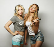 Filles de beauté avec un microphone chantant et dansant Photos libres de droits