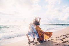 Filles de Boho marchant sur la plage Photographie stock