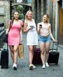 Filles de déplacement marchant avec des valises dans la ville Photos libres de droits