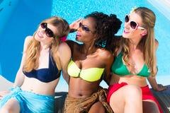 Filles de diversité s'asseyant sur la piscine dans la détente d'été Image stock