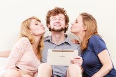 Filles de femmes embrassant le type d'homme avec le comprimé Amusement Images stock