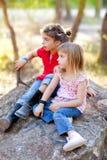 Filles de gosse d'amis jouant dans la roche de forêt Photographie stock libre de droits