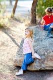 Filles de gosse d'amis jouant dans la roche de forêt Photographie stock