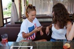 Filles de hippie à l'aide du téléphone de cellules pendant le petit déjeuner de matin dans le restaurant moderne Photographie stock