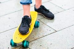 Filles de hippie avec la planche à roulettes dehors sous la pluie Skatebord de plan rapproché Femme sportive active ayant l'amuse Image libre de droits