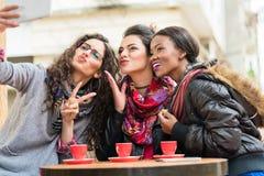 Filles de hippie dans le café faisant un selfie avec le comprimé Images libres de droits