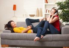 Filles de l'adolescence écoutant la musique sur le divan Photographie stock