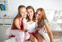Filles de l'adolescence avec le bâton de selfie photographiant à la maison Image libre de droits