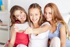 Filles de l'adolescence avec le smartphone prenant le selfie à la maison Photos libres de droits