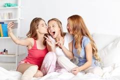Filles de l'adolescence avec le smartphone prenant le selfie à la maison Photographie stock libre de droits