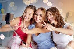 Filles de l'adolescence avec le smartphone prenant le selfie à la maison Images stock