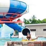 Filles de l'adolescence ayant l'amusement avec de grands glisseurs dans le parc d'aqua Images libres de droits