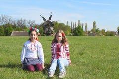 Filles de l'adolescence dans des vêtements nationaux se reposant sur l'herbe dans la campagne Image stock