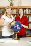 Filles de l'adolescence dans la bibliothèque avec le globe Photographie stock libre de droits