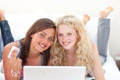 Filles de l'adolescence faisant des emplettes en ligne dans une chambre à coucher Image libre de droits