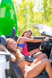 Filles de l'adolescence folles heureuses de surfer souriant sur la voiture Images stock