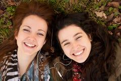 Filles de l'adolescence heureuses partageant la musique Photographie stock