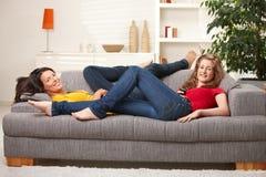 Filles de l'adolescence heureuses souriant sur le sofa Image stock