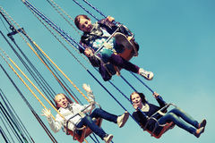 Filles de l'adolescence heureuses sur le carrousel à chaînes d'oscillation Photographie stock libre de droits