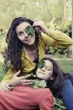 Filles de l'adolescence jouant avec des feuilles dans un jardin Photographie stock libre de droits