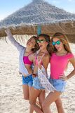 Filles de l'adolescence de meilleurs amis sous le parapluie de chaume Photographie stock