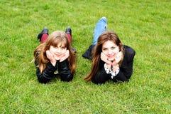 Filles de l'adolescence s'étendant sur l'herbe verte Photos libres de droits