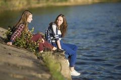 Filles de l'adolescence s'asseyant sur un pilier près de l'eau nature Images libres de droits
