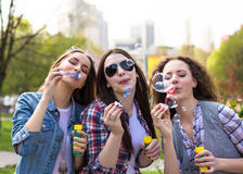 Filles de l'adolescence soufflant des bulles de savon Jeunes adolescents heureux ayant l'amusement dans le parc d'été Image stock