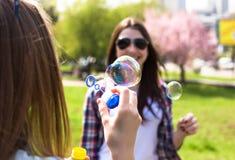 Filles de l'adolescence soufflant des bulles de savon Jeunes adolescents heureux ayant l'amusement dans le parc d'été Images libres de droits