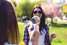 Filles de l'adolescence soufflant des bulles de savon Jeunes adolescents heureux ayant l'amusement dans le parc d'été Photographie stock