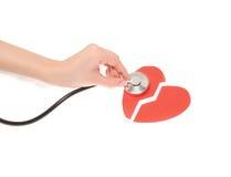 Filles de mains avec un stéthoscope et un coeur brisé deux Photo libre de droits